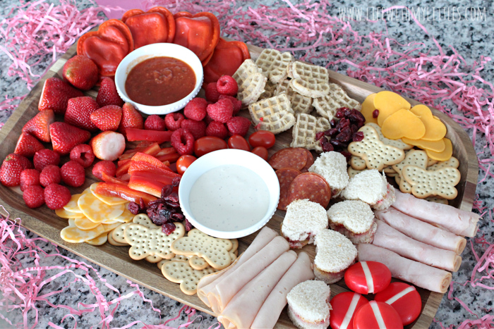 This kid-friendly Valentine's Day charcuterie board is such a fun idea for lunch or dinner. It's easy to put together, and there are lots of great pink and red food suggestions included so you can make your own! Making a charcuterie board for kids has never been easier!